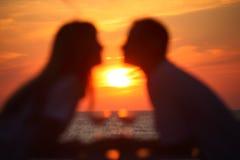 Les silhouettes du couple brouillé sur le coucher du soleil Photos stock