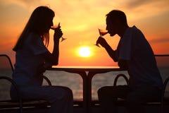 Les silhouettes du couple sur le coucher du soleil derrière la table Images libres de droits