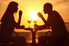 Les silhouettes du couple sur le coucher du soleil se reposent à la table Images stock