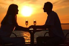 Les silhouettes du couple sur le coucher du soleil se reposent à la table Photo stock