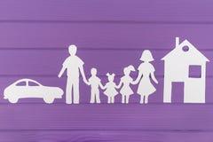 Les silhouettes ont coupé du papier de l'homme et femme avec deux filles et maisons et voitures de garçon près Image libre de droits