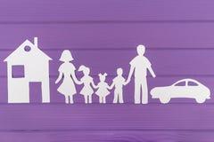 Les silhouettes ont coupé du papier de l'homme et femme avec deux filles et maisons et voitures de garçon près Images libres de droits