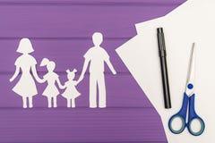 Les silhouettes ont coupé du papier de l'homme et de la femme avec deux filles Photos libres de droits