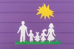 Les silhouettes ont coupé du papier de l'homme et de la femme avec deux filles et garçon sur l'herbe sous le soleil Photographie stock