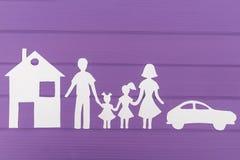 Les silhouettes ont coupé du papier de l'homme et de la femme avec deux filles, maisons et voitures près Photos libres de droits
