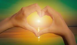 Les silhouettes remettent en forme de coeur avec le coucher du soleil et le fond de mer vi Photo stock