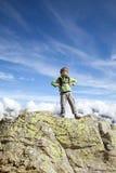 Les six années de garçon se tient sur la grande roche Photographie stock libre de droits
