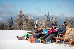 Les skieurs d'amis détendent dans les chaises sur le dessus de montagne Photographie stock libre de droits