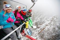 Les skieurs d'amis sur le remonte-pente montent sur la pente de ski au jour neigeux Image stock