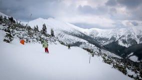 Les skieurs et les surfeurs montant sur un ski inclinent Photo stock