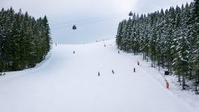 Les skieurs et les surfeurs montant sur un ski inclinent Images libres de droits