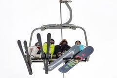 Les skieurs et les surfeurs s'assied sur le télésiège Image libre de droits