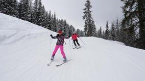 Les skieurs ont l'amusement skiant en bas de la montagne en hiver banque de vidéos