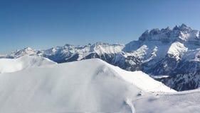 Les skieurs se laissent tomber vers le bas dans la vallée Image stock