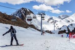 Les skieurs se tenant sur le ski neigeux de cirque de montagne inclinent au jour ensoleillé sur le fond d'hiver d'ascenseur de ch Photographie stock