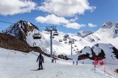 Les skieurs se tenant sur le ski neigeux de cirque de montagne inclinent au jour ensoleillé sur les ascenseurs de chaise et le fo Image stock