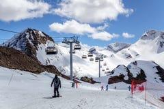 Les skieurs se tenant sur le ski neigeux de cirque de montagne inclinent au jour ensoleillé sur les ascenseurs de chaise et le fo Photo stock