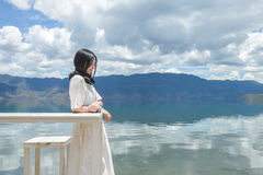 Les smilles de fille se penchant sur la haute table par le lac encaissent Photos stock