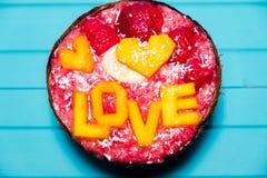 Les Smoothies roulent avec amour de fruit et d'inscription de mangue sur le fond en bois de turquoise Photographie stock libre de droits