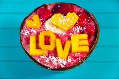 Les Smoothies roulent avec amour de fruit et d'inscription de mangue sur le fond en bois de turquoise, vue supérieure Photos stock