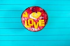 Les Smoothies roulent avec le fruit et l'amour d'inscription de la mangue sur le fond en bois de turquoise, copient l'espace Images stock