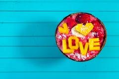 Les Smoothies roulent avec le fruit et l'amour d'inscription de la mangue sur le fond en bois de turquoise, copient l'espace Vue  Photo stock