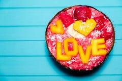 Les Smoothies roulent avec le fruit et l'amour d'inscription de la mangue sur le fond de turquoise, copient l'espace Image stock