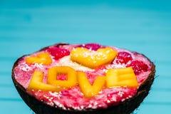 Les Smoothies roulent avec le fruit et l'amour d'inscription de la mangue sur un fond en bois bleu, copient l'espace Images stock