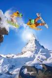 Les Snowboarders sautant contre le ciel bleu Image stock