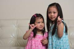 Les soeurs asiatiques tenant des mains aiment des surfers Photo stock