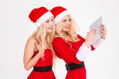 Les soeurs attirantes heureuses jumelle faire le selfie utilisant le comprimé Photographie stock libre de droits