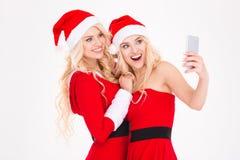 Les soeurs blondes gaies jumelle faire le selfie utilisant le téléphone portable Photographie stock libre de droits
