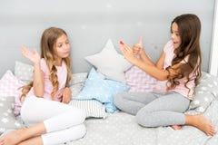 Les soeurs dans des pyjamas détendent la chambre à coucher et prennent la photo drôle pour le compte social de réseau Loisirs et  images stock