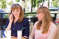 Les soeurs de jumeaux ont des coctails au restaurant images libres de droits