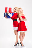 Les soeurs heureuses et bouleversées jumelle dans des costumes de Santa partageant des cadeaux Images stock