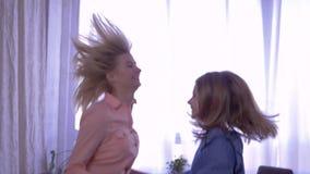Les soeurs heureuses ont l'amusement ensemble et le saut sur le lit tenant des mains à la maison banque de vidéos