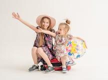 Les soeurs heureuses s'asseyent sur une valise Image stock