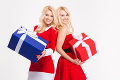 Les soeurs joyeuses jumelle dans des costumes du père noël posant avec des présents Photos stock
