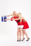Les soeurs jumelle dans des costumes rouges du père noël dupant avec des cadeaux Photo libre de droits