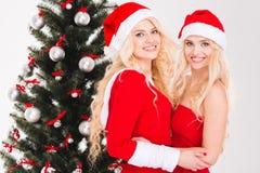 Les soeurs jumelle dans des vêtements du père noël posant près de l'arbre de Noël Photographie stock