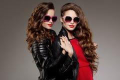 Les soeurs jumelle en verres de soleil de hippie riant deux mannequins Photos stock
