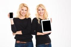 Les soeurs jumelle montrer le smartphone et la tablette avec les écrans vides Images stock