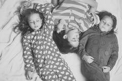 Les soeurs ou les amis dans des pyjamas dorment dans le lit, vue supérieure Photos libres de droits