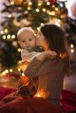 Les soeurs près de l'arbre de Noël, la fille la plus âgée tient le bébé photographie stock libre de droits