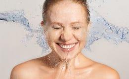 Les soins de la peau heureux de femme de beauté, lavant avec éclaboussent de l'eau images libres de droits