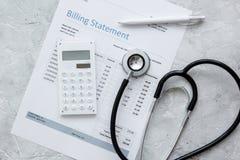Les soins de santé coûtent avec la déclaration, le stéthoscope et la calculatrice de facturation sur la vue supérieure en pierre  images libres de droits