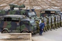 Les soldats allemands de police militaire défend un secteur contre le rôle jouant des démonstrateurs images stock