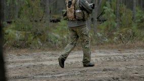 Les soldats dans le camouflage avec des armes de combat font leur manière en dehors de la forêt, dans le but de la capturer, les  clips vidéos