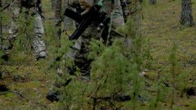 Les soldats dans le camouflage avec des armes de combat font leur manière en dehors de la forêt, dans le but de la capturer, les  banque de vidéos