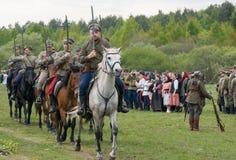 Les soldats de cavalerie montent sur des chevaux avec les épées nues Image libre de droits